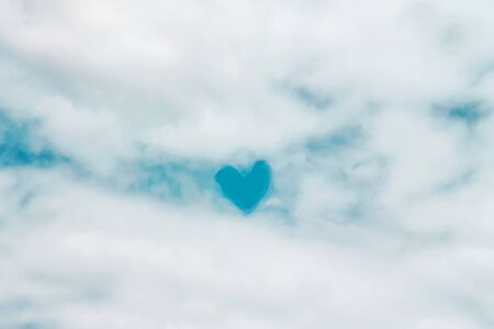 Fluffy white clouds patterns with bright blue heart shaped on sky for natural background