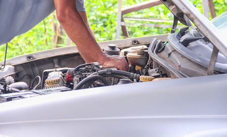 Automotive mechanic checking up of old car machine , open hood close up