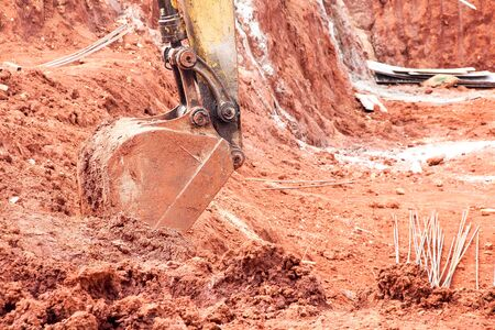 Excavator parked in red soil at construction site background Stockfoto