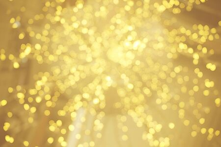 Gold bokeh sparkle glitter from light bulb abstract patterns for Christmas and Happy new year background Stock Photo