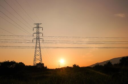 High voltage pole on sunset sky background,  silhouette of tree and mountains  rural landscape in the evening Banque d'images - 130774599