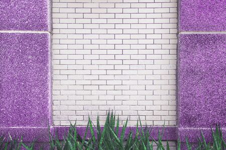 White brick wall with purple marble pole patterns and green leaf plant on background ,copy spcae Stock Photo