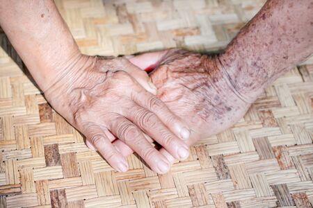 Asian grandma and grandpa hands on background