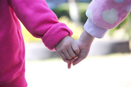 Petit frère tenant les mains de sa sœur aînée, arrière-plan asiatique pour deux personnes