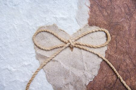 Paper torn in heart shaped  with bow rope patterns on white and brown mulberry paper for valentine day or wedding card background Stockfoto