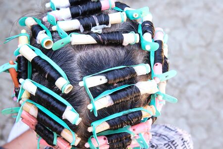 Elderly asian woman  head and colorful plastic rollers with hair perm solution , curling process background