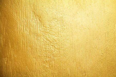 Muro de hormigón de pintura dorada textura antigua o fondo amarillo Foto de archivo