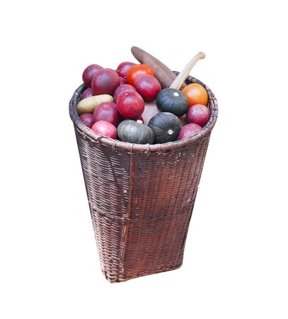 Old woven bamboo basket with vegetables and fruits isolated on white background