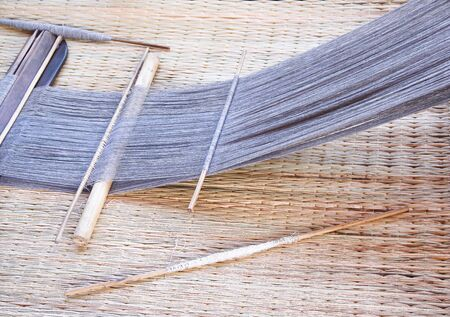 Yarn in weaving textile equipment on straw mat background