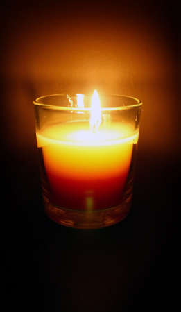 una piccola candela illumina una camera oscura