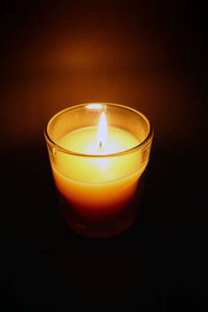 a small candle brightens a dark room