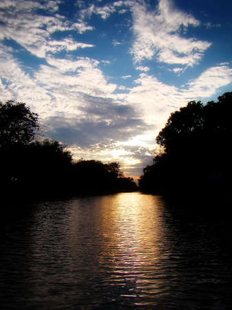 the sun sets beyond a canal in illinois                               Stock Photo