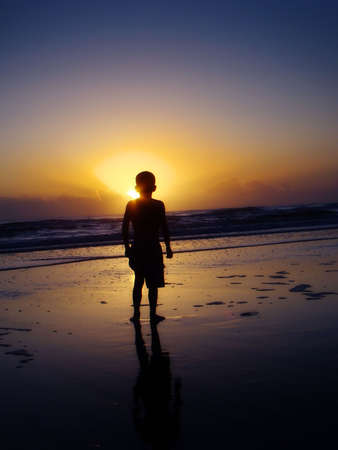 silhouette of a boy watching the sunrise at the beach