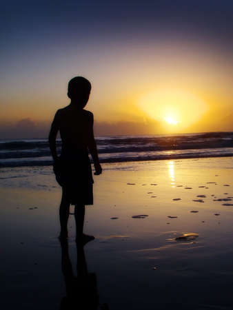 silhouette of a boy watching the sunrise at the beach                       Stock Photo