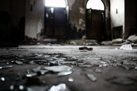 broken glass on the floor of a lobby of an old abandoned apartment building
