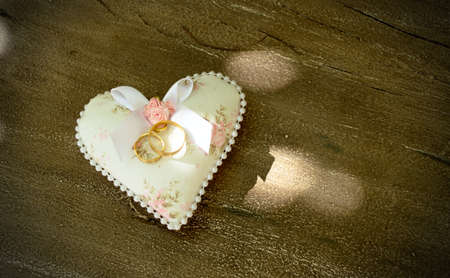 alliances: wedding rings on heart and wood background Stock Photo