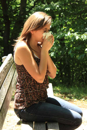 Young woman in the park blowing her nose Stock Photo