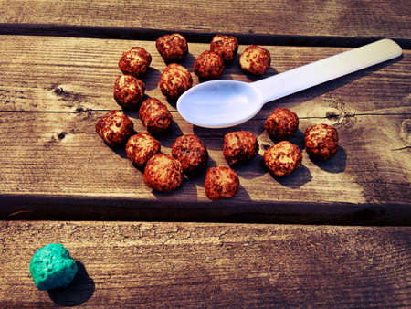 outsider: The brown snack balls huddle around the spoon, wondering what it is, while the blue ball knows better. Stock Photo
