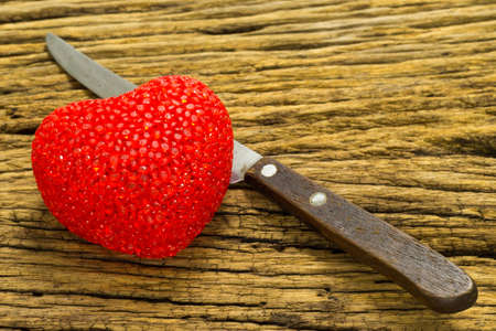 Knife and heart on wooden background. Stock Photo