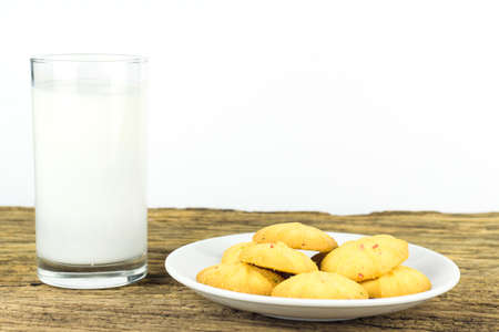 quadratic: Cookies in dish with a glass of cold milk on wooden table and white background.