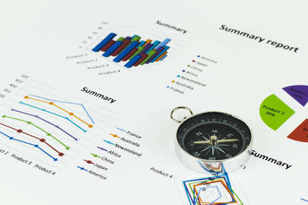 Bussiness graphs and finances with a compass lying nearby. Stock Photo