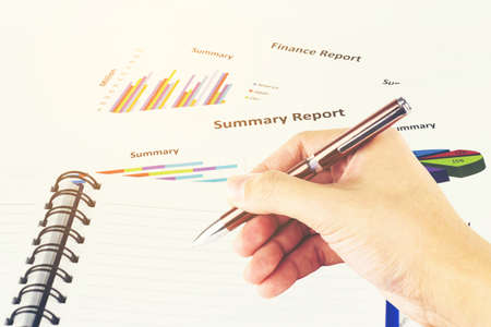 Pen in the mans hand, calculations,finances and analysis of the market concept. Stock Photo