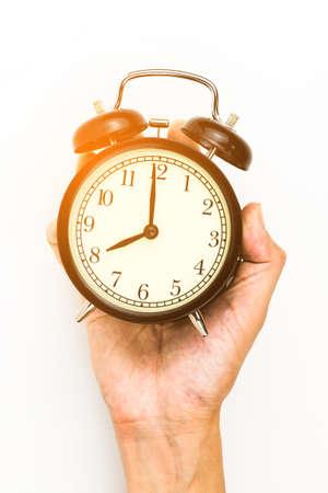 chrome man: Mans Hand holding a alarm clock.
