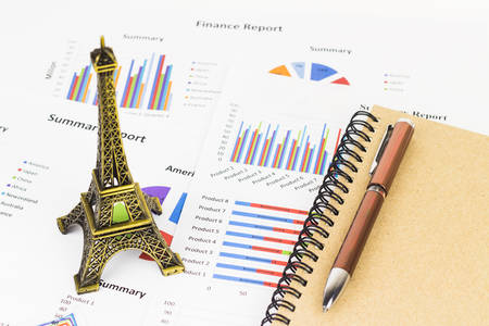 Business savings, finances and analysis economy concept with Eiffel tower replica.