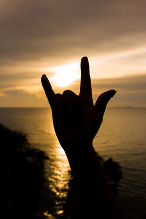 indication: Silhouette Hand with love fingers with sunset sea blackground.