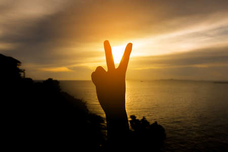Silhouette Hand with two fingers concept of victory with sunset sea blackground.