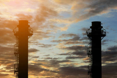 Silhouette Natural Gas Combined Cycle Power plant electricity generating station of industry in sunset sky. Stock Photo