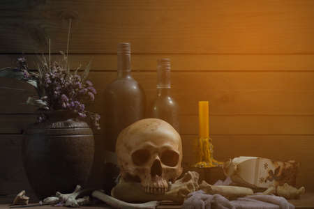 captives: Still Life of skull and bone with fetters and candle on the wooden plank in dim light night  Select focus. Stock Photo