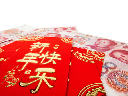 Chinese red envelopes over Chinese money hundred yuan banknotes pile isolated on white background. Chinese text on envelope meaning Happy Chinese New Year.