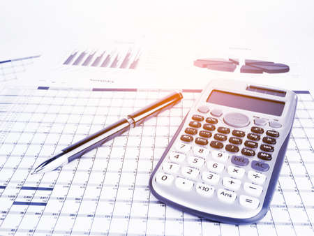 Calculator and pen with business graphs and report information background for financial and economy concepts, Blue tone.
