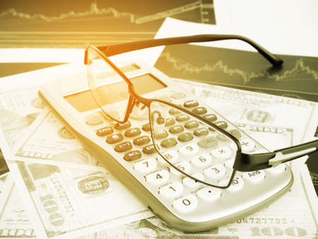 Calculator and glasses with business graphs and report information background for financial and economy concepts, Vintage tone. Stock Photo