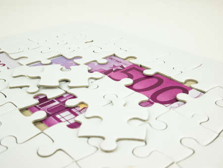 Missing jigsaw puzzle pieces on Five hundred 500 Euro bills banknotes background, Business solution concept, Key for success concept.