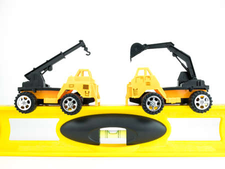 Toy Crane car and Mechanical digger with building level on white background, Engineering construction concept.