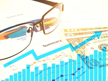Business chart near dollars by unfocused glasses, Financial concept. Stock Photo