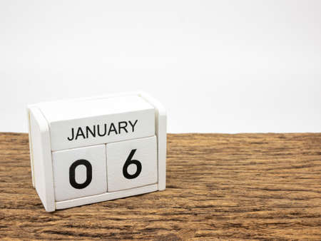 January 6 white cube wooden calendar on vintage wood and white background with winter day, Copyspace for text.