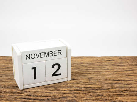 November 12 white cube wooden calendar on vintage wood and white background with autumn day, Copyspace for text. Foto de archivo