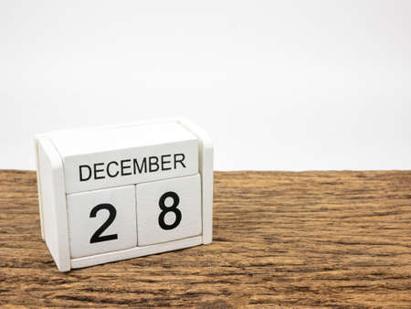 December 28 white cube wooden calendar on vintage wood and white background with winter day, Copyspace for text.