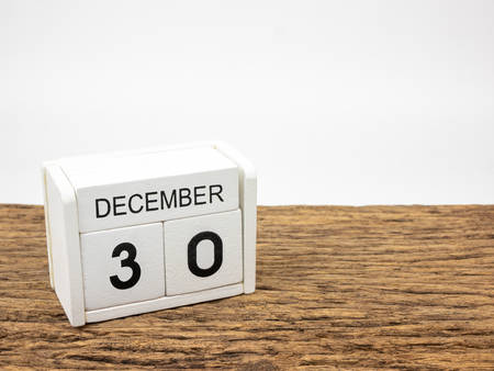 December 30 white cube wooden calendar on vintage wood and white background with winter day, Copyspace for text.