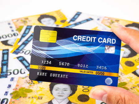 Blue worldwide credit card on korea banknotes background.