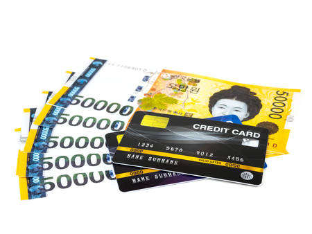 Credit card with South Korea Won Banknotes isolated on white background.