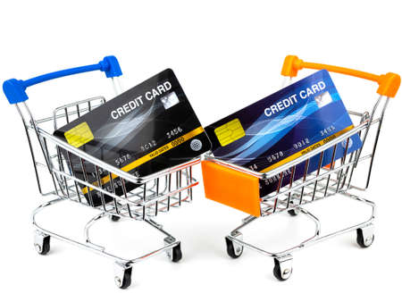 Credit cards in small shopping cart isolated on white background.