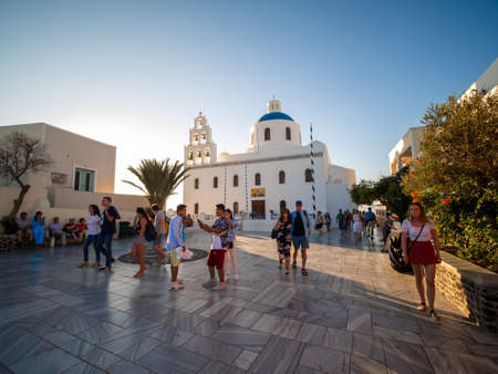 SANTORINI, GREECE JULY. 28, 2019 Traveler Crowd at White Christian church with domes, bells and sunset.
