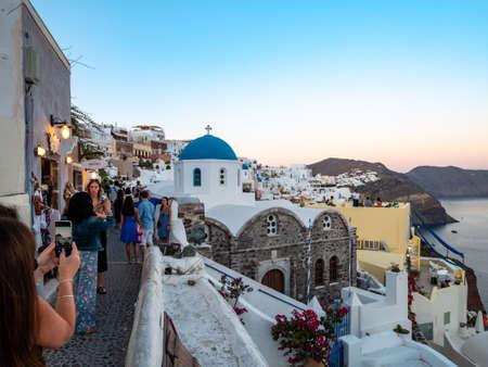 SANTORINI, GREECE JULY. 28, 2019 The tourist island of santorini where tourists watch the sunset