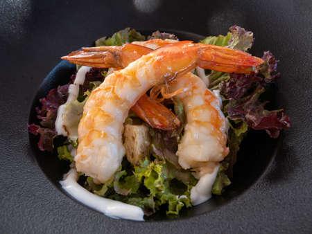 Shrimp caesar salad in white plate, Mediterranean cuisine. Фото со стока