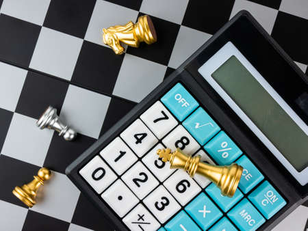 Financial games concept, Game of chess with calculator, selective focus.