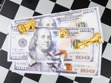 Finanzspielkonzept, Schachspiel mit Dollargeld, selektiver Fokus.